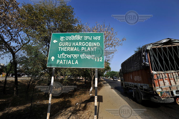 A bilingual sign on a road giving directions to the Guru Hargobind Thermal Power Plant, and Patiala.