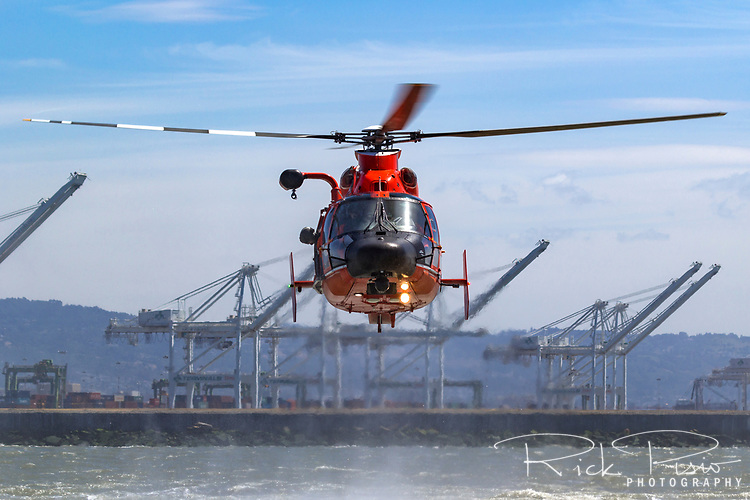 United States Coast Guard MH-65 Dolphin hovers over the waters of San Francisco Bay.