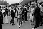 St Johns Wood, London. England. 1975<br /> At the Eton v Harrow annual cricket match at Lords. An old Etonian walks through a group of casually dressed scholars. He is wearing a grey topper and matching velvet trimmed double breasted Regency style cutaway tail coat, with a wing collared shirt and cravat. Buckskin grey gloves and black and white two-tone shoes complete his ensemble. Surely, the height of sartorial elegance?