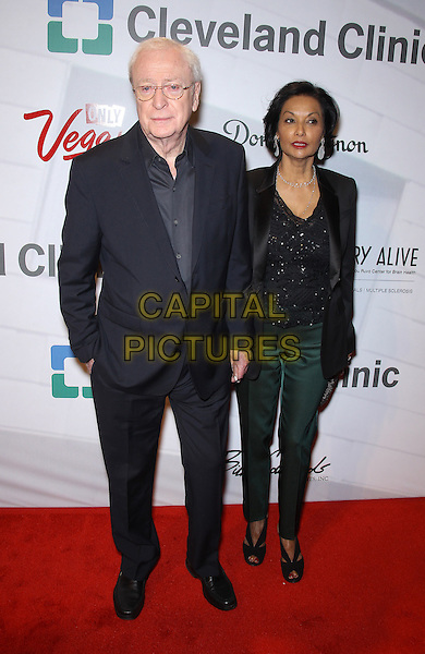"""Sir Michael Caine, Shakira Caine.Attending Keep Memory Alive's 17th Annual """"Power of Love Gala"""" honors Quincy Jones and Sir Michael Caine with 80th Birthday Celebration at MGM Grand, Las Vegas, NV, USA, 13th April 2013..full length blue navy suit shirt black husband wf married green trousers  top sparkly .CAP/ADM/MJT.© MJT/AdMedia/Capital Pictures"""