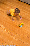 10 month old baby boy crawling to reach toy