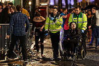 Pictured: A woman is moved away in a wheelchair by St John Ambulance staff. Sunday 31 December 2017 and 01 January 2018<br /> Re: New Year revellers in Wind Street, Swansea, Wales, UK