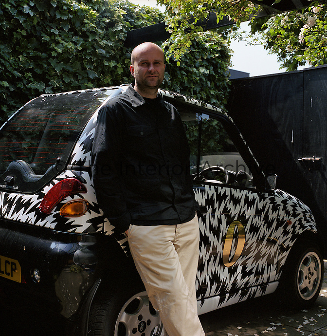 Portrait of designer Jason Maclean leaning against a black and white electric car