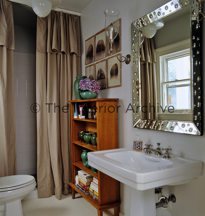 The double fabric shower curtain and the wooden bookcase and artwork give the bathroom the feel of a living room
