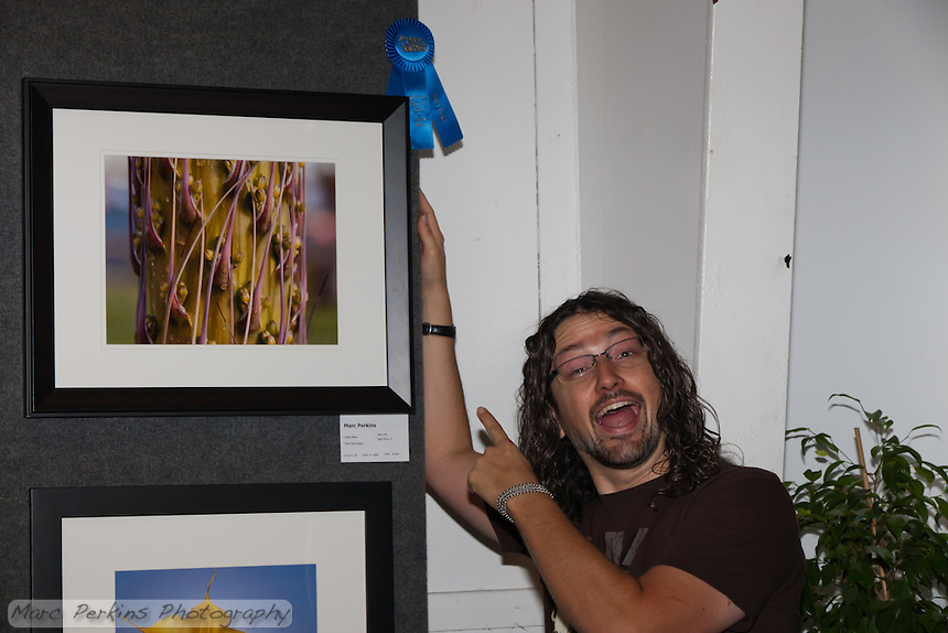 A picture of me with my winning entry at the 2011 Orange County Fair.  The first place blue ribbon is so pretty!  My photograph was in the amateur color print of plants category.  Many thanks to Nafis, who kindly took this picture of me.