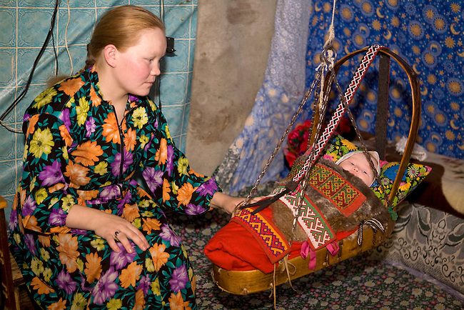 Maria, a young Khanty woman, rocks her baby, Zhana, in a traditional cradle at a fishing camp on the River Ob. Yamal, Western Siberia.