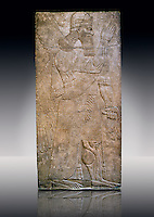 Assyrian relief sculpture panel  of a protective spirits holding a bucket of holy water wearing a rosette bracelet which symbolises divine power. From Nimrud, Iraq.  865-860 B.C North West Palace, Room S, door c.  British Museum Assyrian  Archaeological exhibit  ref WA 118803