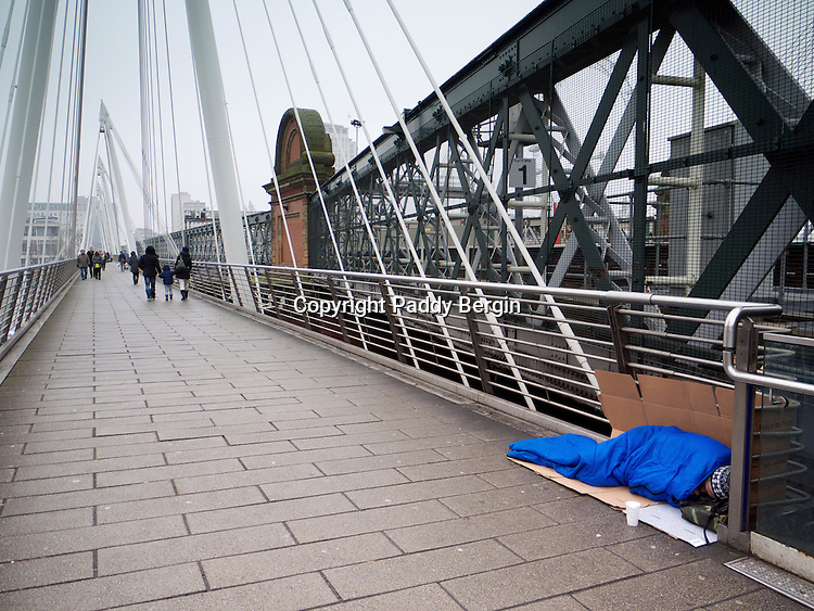 Homeless person sleeping on Hungerford Bridge in the rain.<br /> <br /> Homelessness is the condition of people without a regular dwelling. People who are homeless are most often unable to acquire and maintain regular, safe, secure, and adequate housing, or lack &quot;fixed, regular, and adequate night-time residence.&quot;<br /> <br /> The term homeless may also include people whose primary night-time residence is in a homeless shelter, a warming centre and a domestic violence shelter.<br /> <br /> Stock Photo by Paddy Bergin