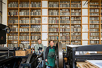 A 19th-century Paris printworks is defying its age and serving as a creative hub for contemporary artists. Printers Em-Khindelvert and Soukaloun Thoune, with four-metre-high stacks of lithographic stones behind them.