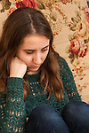 20 year old young adult woman sitting looking down depressed expression