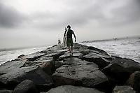 A surfer walks out on the jetty at Far Rockaway beach in New York, United States, in the early morning of 17 September 2005. Photo Credit: David Brabyn.