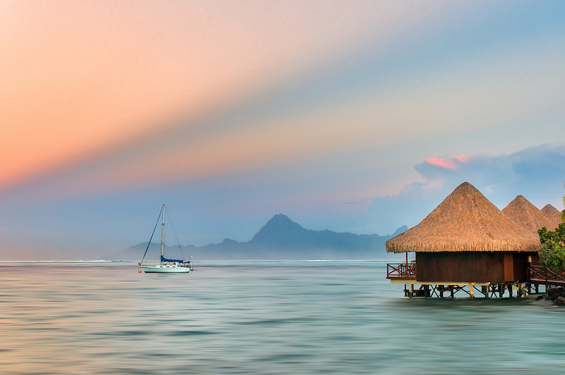 Over the water bungalows and sailboat with sunrise and Moorea in back. Tahiti