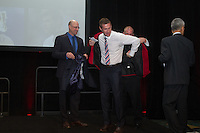 San Francisco, CA - Saturday Feb. 14, 2015: (Left to right): Kasey Keller watches as  Matt McBride places the US Soccer Hall of Fame jacket on  US Soccer player Brian McBride as US Soccer president Sunil Gulati looks on.  Brian McBride was inducted into the hall of fame at the 2014 US Soccer Hall of Fame Induction ceremony.