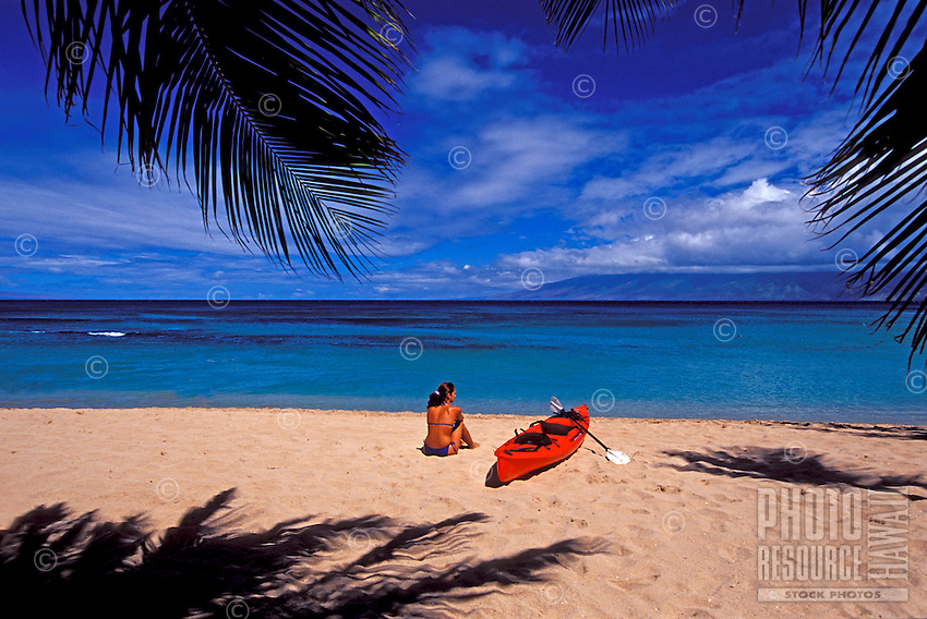 Girl on the beach with red kayak at Napili Bay, Maui.