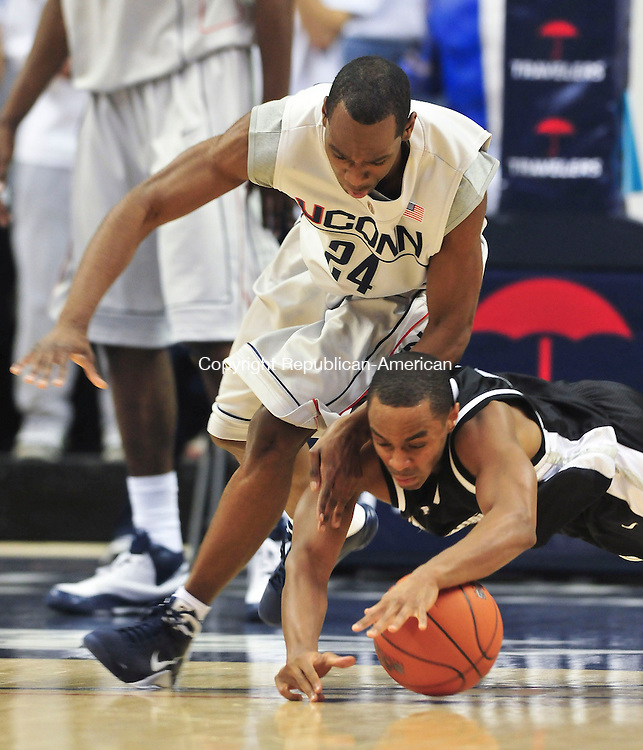 STORRS, CT--013109JS10-- UConn's Craig Austrie (24) and between Providence's Sharaud Curry (4) dive for a loose ball during their game Saturday at the Gampel Pavilion in Storrs.<br /> Jim Shannon/Republican-American