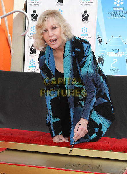 Kim Novak.Kim Novak Immortalized With Hand And Footprint Ceremony As Part Of The 2012 TCM Classic Film Held at Grauman's Chinese Theatre,  Hollywood, California, USA, 14th April 2012..half length top kneeling black green blue  jacket cardigan writing signing name autograph in cement .CAP/ADM/KB.©Kevan Brooks/AdMedia/Capital Pictures.