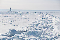 Ice clings to a breakwater and lighthouse on Lake Superior in Marquette Michigan in winter.