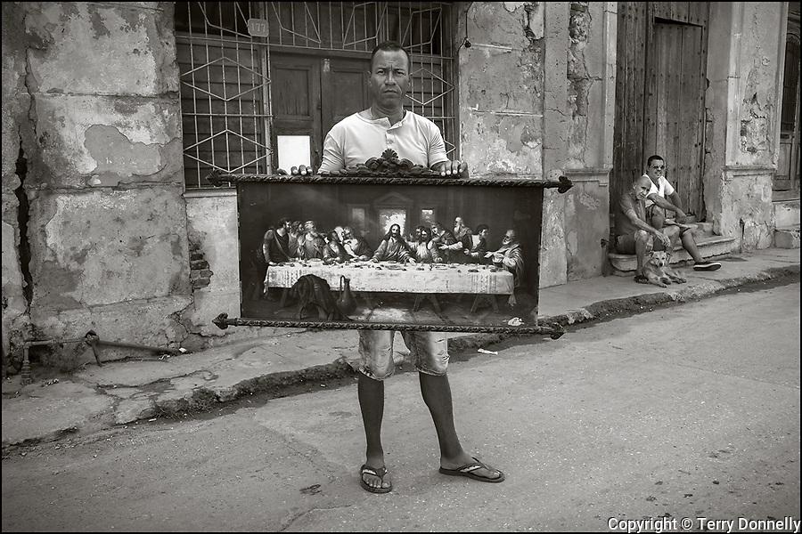 Regla, Havana, Cuba:<br /> Street scene man with painting of the Last Supper in the Regla nieghborhood
