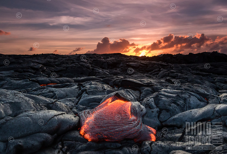 Lava Sunrise: Lava oozes out onto the 61g lava flow field as the sun rises along the horizon, Hawai'i Volcanoes National Park, Big Island.