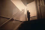 man at top of stairs with wall shadow