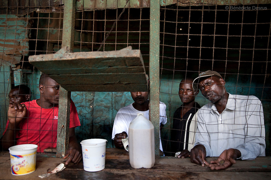 Customers buy Busaa, a traditional fermented beer, at the Madiaba Busaa Club in a Nairobi slum on april 7, 2013. Busaa is made by crudely fermenting maize, millet, sorghum or molasses. At Kshs 35 per liter it is much cheaper than a Kshs120 half-liter bottle of commercial beer. The local brew was legalised in 2010 and since then busaa clubs have become increasingly popular. Drinking is on the rise in Kenya, especially among young people. Photo by Benedicte Desrus