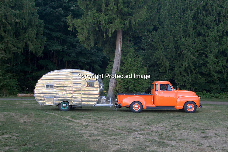 An orange crush 3100 Chevrolet pulling a shiny aluminum finish 1954 Cardinal vintage travel trailer canned ham.