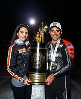 Nov 12, 2017; Pomona, CA, USA; NHRA pro stock motorcycle rider Eddie Krawiec poses for a portrait with wife Anne Marie Krawiec the trophy after clinching the 2017 world championship during the Auto Club Finals at Auto Club Raceway at Pomona. Mandatory Credit: Mark J. Rebilas-USA TODAY Sports