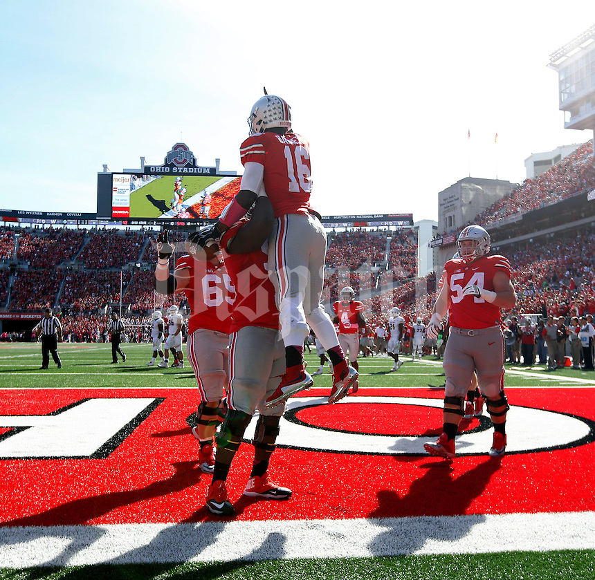 Ohio State Buckeyes quarterback J.T. Barrett (16) is held up in the air by Ohio State Buckeyes offensive lineman Chase Farris (57) after scoring a rushing touchdown against Maryland Terrapins in the fourth quarter of their game in Ohio Stadium on October 10, 2015.  (Dispatch photo by Kyle Robertson)