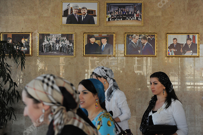 In a concert hall in Grozny, the Chechen capital, women walked past photographs of the Chechen president Ramzan Kadyrov meeting with Chechen, Russian and world leaders. September 7, 2011