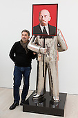 """London, UK. 25 November 2014. Installations from the series """"Paradies Lost"""" by Grisha Bruskin. Grisha Bruskin stands next to his arwork Man with a portrait of Lenin. Press preview of the new exhibition Post Pop: East Meets West at the Saatchi Gallery, London. The Tsukanov Family Foundation and Saatchi Gallery present the first comprehensive exhibition examining why Pop Art has had such a powerful influence over artists from world regions that had or still have very different and sometimes opposing ideologies. The exhibition brings together 250 works by 110 renowned artists from China, the Former Soviet Union, Taiwan, the UK and USA in the largest survey to date exploring Pop Art's enduring legacy. The exhibition is open to the public from 26 November 2014 to 23 February 2015, admission is free. Photo: Bettina Strenske"""