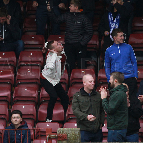 7th October 2017, Glanford Park, Scunthorpe, England; EFL League One football, Scunthorpe versus Wigan; A Wigan Athletic fan taunts the Scunthorpe United fans after his side went 0-2 ahead