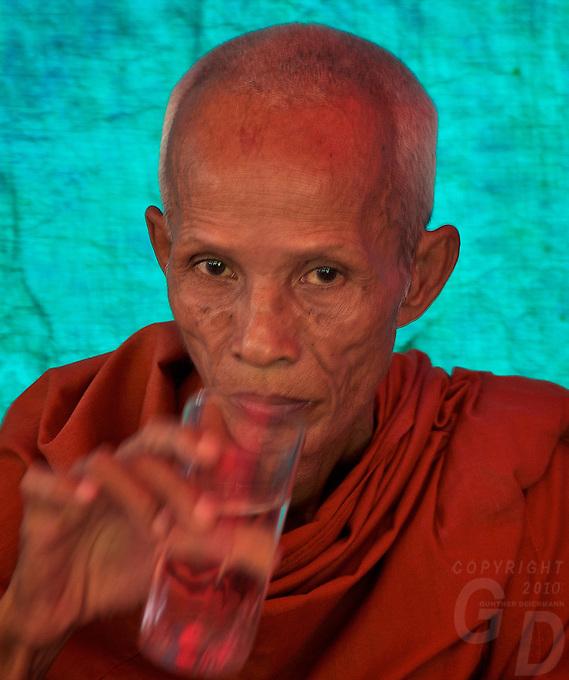 Buddhist Monk near Aek Phnom Angkorian Temple, a local funeral ceremony in a Village near Battambang Cambodia,