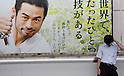 Tokyo, Japan - A tired Japanese salaryman stands in front of a billboard advertisement promoting refreshing beer at Shinjuku station. Morning commuters typically spend over one hour on the train going to work. Trains are usually so packed that train platform staff have to push commuters to fit in the train so that the doors can close shut. (Photo by Yumeto Yamazaki/AFLO)