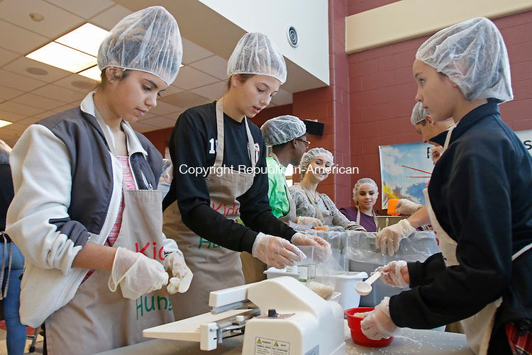 Terryville, CT-112115MK03 (from front left) Mikaela Corsi and Mackenzie with Mackenzie Cowles prepare meals for the needy during the third annual volunteer project at Terryville High School Saturday afternoon.  Lisa Aiudi, event coordinator said that the Terryville High School's Leo Club raised four-thousand dollars to purchase the food supplies from Harvest Pack.  The supplies were mixed, by 160 volunteers, to create packages that will serve six people at a time. The event ran for four hours by two shifts of volunteers and prepared enough containers to serve twenty-thousand meals.  The club's efforts will be distributed to local food pantries and to the needy abroad.  Michael Kabelka / Republican-American