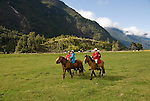 Chile, Lake Country: People riding horses at Peulla in a meadow in the Andes..Photo #: ch609-33255..Photo copyright Lee Foster www.fostertravel.com, lee@fostertravel.com, 510-549-2202.