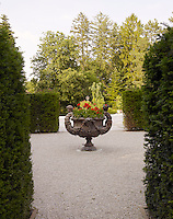 A classical urn filled with red geraniums is the centrepoint of a gravel walkway framed by box hedges