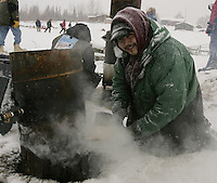 Nikolai resident and Iditarod volunteer checker and helper Daryl Petruska adds wood to a fire to keep water hot for the mushers.