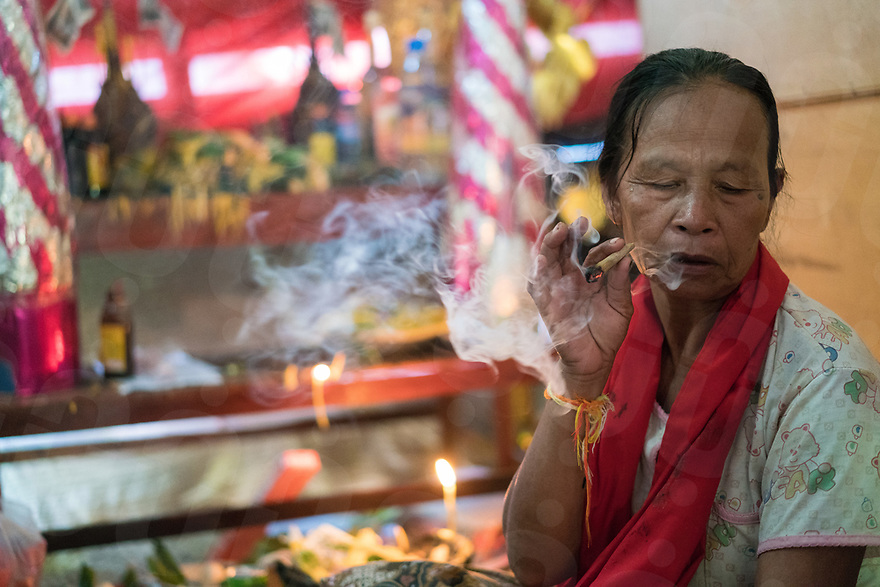 May 1st, 2017 - Nakasang (Laos). Phoutan smokes at home next to her shrine. Smoking is one sign that Phoutan is in a trance and possessed by the spirit. © Thomas Cristofoletti / Ruom