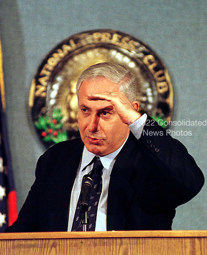 Washington, DC - January 21, 1998 -- Prime Minister Binyamin Netanyahu of Israel shields his eyes from the bright TV lights while answering a reporter's question at the National Press Club..Credit: Ron Sachs / CNP