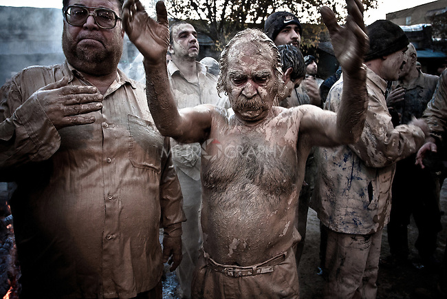 KHORRAMABAD, IRAN : A man covered in mud mourns the death of Imam Hussein during the festival of Ashura...Every year to mark the death of Imam Hussein, Shia Muslims mourn for two days. In Khorramabad and Lorestan in the west of Iran, during the first day of mourning, called Tasooa, women take a vow of silence and go through the streets with the children lighting candles. At 4 am on Ashura, the second day, men cover themselves in mud and then stand in front of a fire until the mud has dried to clay. After this they go to the mosque and pray...Photo by Farhad Babaei/Metrography