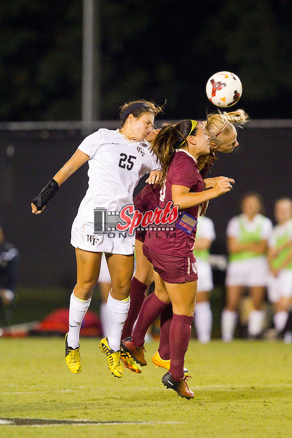 Annick McBryar (25) of the Wake Forest Demon Deacons battles for a jump ball with two Florida State Seminoles defenders during second half action at Spry Soccer Stadium on September 12, 2013 in Winston-Salem, North Carolina.  The Deacons and the Seminoles played to a 0-0 draw.   (Brian Westerholt/Sports On Film)