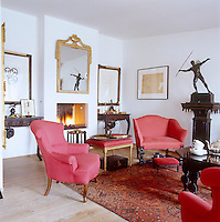 In the living room antique armchairs and sofas are covered in vivid contemporary pink and crimson fabrics and a collection of framed prints by Matisse are displayed on plain white-painted walls