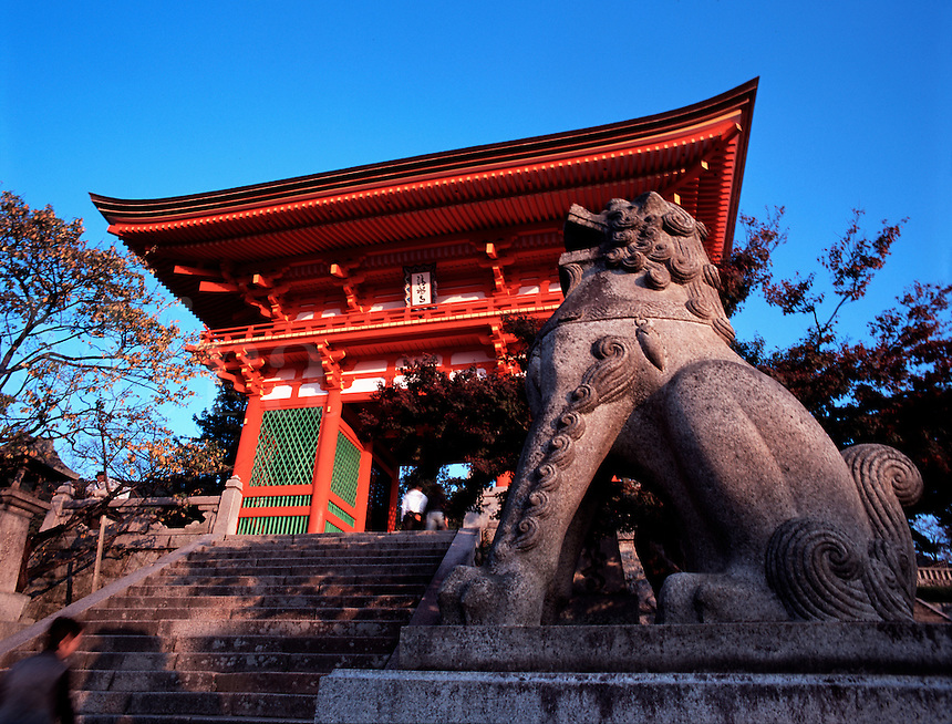 A stone guardian lion sits in front of the main entrance to Kiyomizu Temple, Kyoto, Japa