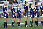 "Montoursville High School girls soccer players pass along a behind the back ""low five"" during the playing of the National Anthem before a game."