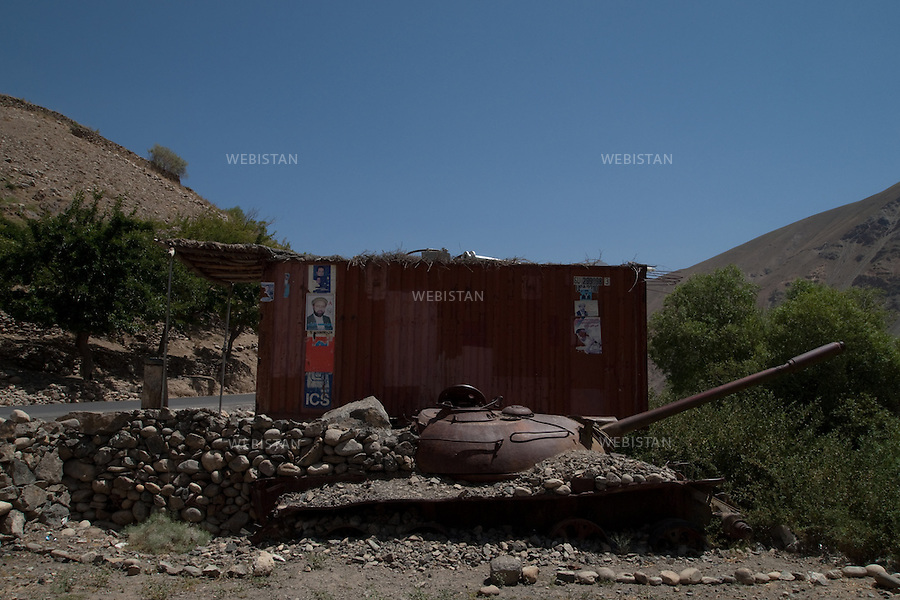 AFGHANISTAN - VALLEE DU PANJSHIR - REGION DE ASTANEH - 16 aout 2009 : carcasse de char pris aux russes par les Moudjahidin du Commandant Massoud lors de la guerre d'Afghanistan de 1979 - 1989 a cote d'un container amenage en boutique sur lequel sont collees des affiches de campagne electorale. La photographie appartient a la serie &quot;Il etait une fois l'Empire Russe&quot;. <br /> <br /> AFGHANISTAN - PANJSHIR VALLEY - ASTANEH REGION  - August 16th, 2009 : The remnants of a Russian tank, seized by Commander Massoud's mujahideen during the Afghan war of 1979-1989, lies next to a container converted into a shop. Campaign posters decorate its outside walls. The photograph is part of the series &quot;Once Upon a Time, the Russian Empire.&quot;
