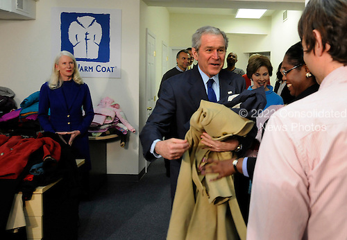 Washington, DC - December 22, 2008 -- United States President George W. Bush and and first lady Laura Bush greet volunteers as they visit the One Warm Coat Holiday Service Project Pathways to Housing in Washington, DC on Monday, December 22, 2008. .Credit: Mike Theiler - Pool via CNP