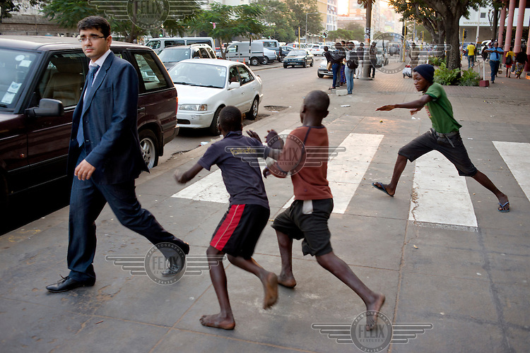 A man dodges some children playing on the pavement.