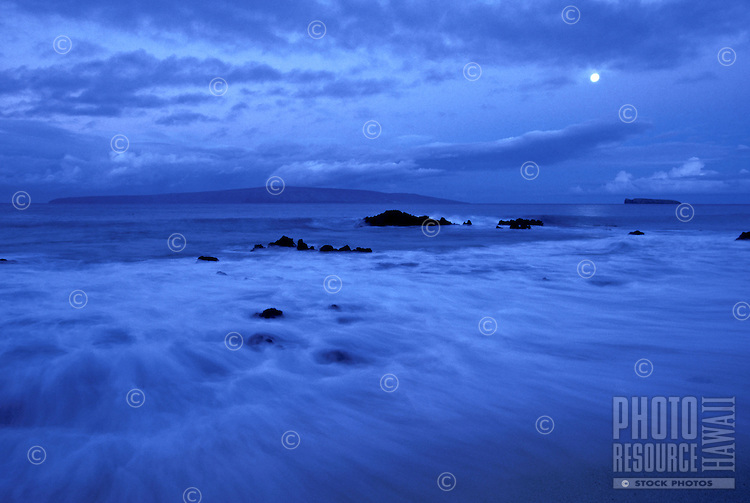 Misty water and lava rocks at Makena, Maui with a full moon setting. Kahoolawe and Molokini in distance.