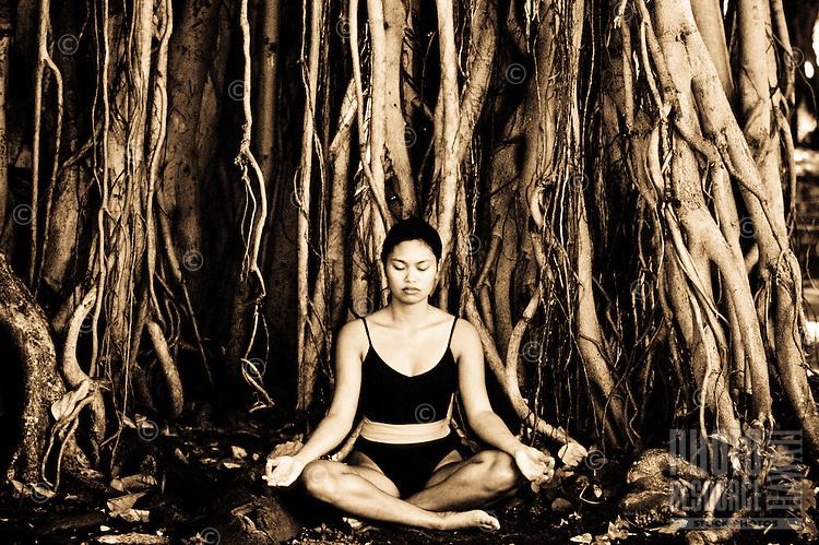 Woman meditating near a banyan tree