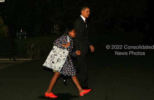 United States President Barack Obama and daughter Sasha leave the White House to board Marine One on the first leg of their trip to Brazil on March 18,2011. .Credit: Dennis Brack / Pool via CNP